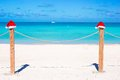 Two Santa Hats On Fence At Tropical White Beach Stock Photo - 40844700