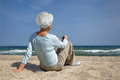 Elderly Woman Sitting In The Sand On The Beach Sea Stock Image - 41092691