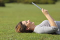 Profile Of A Happy Woman Reading A Tablet Reader On The Grass Stock Photos - 41221783