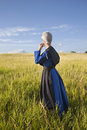 Amish Woman Standing In Grassy Field With Afternoon Sunlight Stock Photos - 41275473