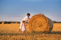 Brother And Baby Sister Pushing Hay Bales In A Field Stock Photo - 41347620