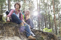 Young Hiking Couple Sitting On Edge Of Cliff In Forest Royalty Free Stock Photography - 41409417