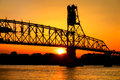Sun By Steel Bridge Silhouette On River At Sunset Royalty Free Stock Photo - 41514655