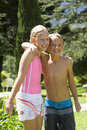 Brother And Sister (7-11) In Swimsuits Arm In Arm In Garden, Smiling, Portrait Stock Photos - 41710973