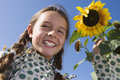 Girl (9-11) Standing Beside Sunflower Growing In Garden, Smiling, Close-up, Portrait, Low Angle View Royalty Free Stock Photo - 41713295