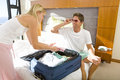 Young Couple Packing Suitcase On Bed, Man Wearing Sunglasses, Smiling At Woman Royalty Free Stock Photo - 41718585