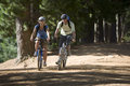 Couple, With Rucksacks And Cycling Helmets, Mountain Biking Along Woodland Trail, Smiling, Front View Stock Photo - 41721850