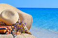 Woman Beach Hat, Bright Towel And Flowers Against Blue Ocean Stock Photography - 41828462