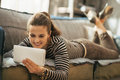 Happy Young Woman Laying On Couch And Using Tablet Stock Image - 41845041