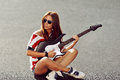 Young Woman Sitting On A Ground And Playing Guitar Royalty Free Stock Image - 42043016