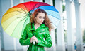 Beautiful Woman In Bright Green Coat Posing In The Rain Holding A Multicolored Umbrella Royalty Free Stock Photography - 42339367