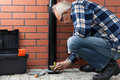 Husband Cleaning Pavement Drain Hole From Autumn Leaves Stock Photo - 42348590