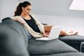 Pretty Young Lady Sitting On Couch Surfing Internet Royalty Free Stock Photo - 42464825