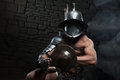 Gladiator In Helmet And Armour Holding Sword Royalty Free Stock Photos - 42994188