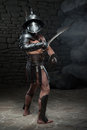 Gladiator In Helmet And Armour Holding Sword Royalty Free Stock Photography - 42994197