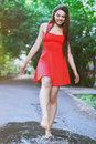 Woman Wearing Red Dress Jumping Into A Puddle After The Rain Stock Photo - 43028580
