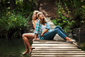 Two Fashion Teen Girls Sitting On The Wooden Bridge Stock Photography - 43117812