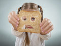 Little Girl Holding Her Face In Front Of A Sad Slice Of Bread Royalty Free Stock Image - 43212116