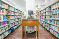 Computer In A Library With Many Books And Shelves Royalty Free Stock Image - 43221256