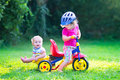 Two Kids On A Bike In The Garden Royalty Free Stock Photo - 43310965