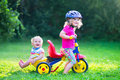 Two Kids On A Bike In The Garden Stock Photos - 43311073