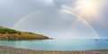 Panorama Of A Rainbow Half Over Sea And Land Stock Image - 43372251
