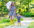 Mother And Little Adorable Child In Yellow Rubber Boots Stock Photos - 43440113