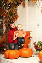 Beautiful Woman With A Child On The Front Porch With Pumpkins Au Royalty Free Stock Image - 43450406