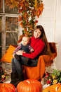 Beautiful Woman With A Child On The Front Porch With Pumpkins Au Stock Photos - 43451333