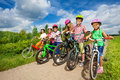 Children In Row Wearing Helmets Holding Bikes Royalty Free Stock Images - 43495689