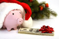 Part Of Piggy Bank With Santa Claus Hat And Stack Of Money American Hundred Dollar Bills With Red Bow And Christmas Tree Standing Stock Image - 43792301