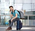 Young Man Sitting On Suitcase And Calling By Cellphone Stock Photos - 43828723