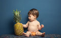Happy Baby Girl Playing With A Pineapple Royalty Free Stock Photo - 43926685