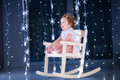 Beautiful Little Toddler Girl  In A White Rocking Chair In A Dark Room With Christmas Lights Stock Images - 44031974