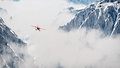 Red Airplane Flying Over Snow Mountains In The Clouds. Royalty Free Stock Images - 44055309