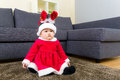 Baby Girl With Christmas Dressing And Seating On Carpet Stock Photo - 44091570