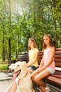 Two Happy Girls Sitting On The Bench In Park Stock Photos - 44101823