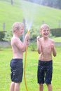 Two Brothers Playing With Water Hose In The Garden Royalty Free Stock Images - 44140889