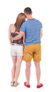 Back View Of Young Embracing Couple In Shorts  Hug And Look. Royalty Free Stock Images - 44176589