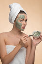 Spa Girl With A  Towel On Her Head Applying Facial Stock Photography - 44177752