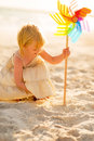Baby Girl Playing With Colorful Windmill Toy Royalty Free Stock Photography - 44274187