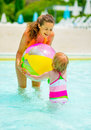 Mother And Baby Playing With Ball In Swimming Pool Stock Images - 44277324