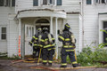Three Firefighters On Fire Scene Walking Into A Building Royalty Free Stock Photography - 44376897