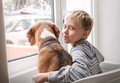 Little Boy With His Dog Waiting Together Near The Window Royalty Free Stock Photo - 44384865