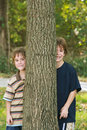 Boys Peeking Around A Tree Stock Photo - 4464210