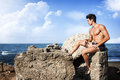 Muscular Guy Sitting On The Rock, Mediterranean Sea Royalty Free Stock Photography - 44642757