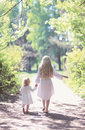 Two Sisters Holding Hands Walking In The Forest Royalty Free Stock Images - 44657979