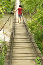 Girl Walking On A Wooden Bridge Over A River Royalty Free Stock Photography - 44713317