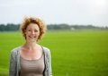 Attractive Woman Smiling Outdoors By Green Countryside Royalty Free Stock Photography - 44754017