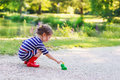 Beautiful Little Girl In Red Rain Boots Playing With Rubber Frog Stock Images - 44770284